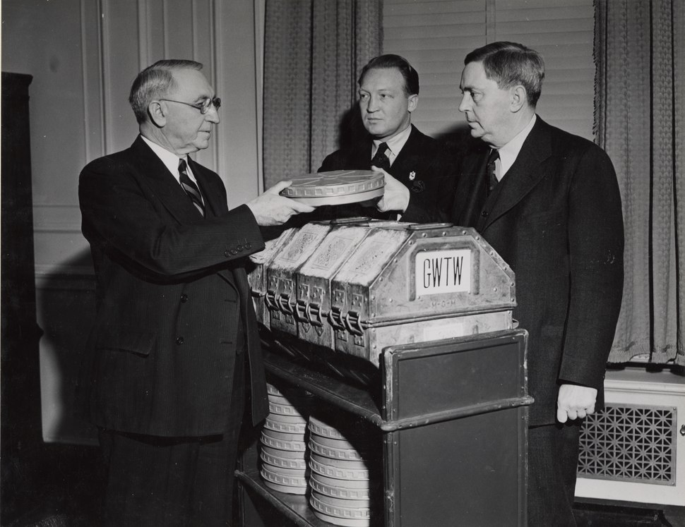 """Photograph of First Archivist of the United States R. D. W. Connor Receiving Film """"Gone With The Wind"""" from Senator George of Georgia and Loew's Eastern Division Manager Carter Barron, 1941"""