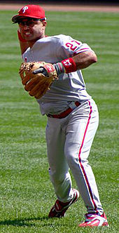 "A man wearing a gray baseball uniform with ""Phillies"" across the chest in red script and a red baseball cap throws a baseball with his right hand."