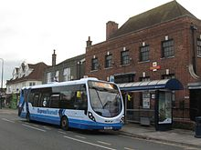 Pale grey bus with blue markings in front of a brick building