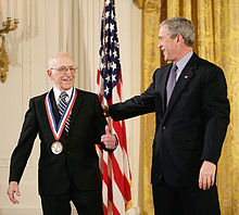 Photo de Georges Bush félicitant Ralph Baer, médaille nationale de la technologie et de l'innovation autour du cou