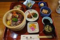 Rice bowl topped with Sashimi combo with small dishes on a lunch tray (13807769445).jpg