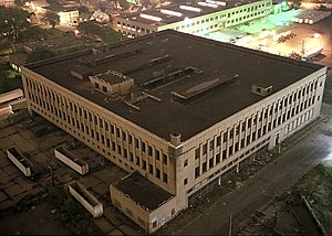 Roosevelt Warehouse - The Roosevelt warehouse Detroit school book depository building in August 2000, after being damaged by fire and abandoned. View from a taller adjacent building at night. Small trees are visible growing on the third floor beneath a hole in the roof.