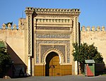 A picture of a large gate several metres high covered with various abstract designs.