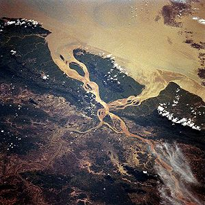 River bifurcation - River deltas such as the pictured delta of the Salween River in Myanmar often show bifurcations. The water flows in from the lower section of the image and passes on both sides of the large island in the center.