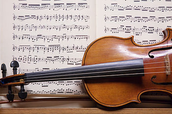 English: Violin with sheet music in a repair s...