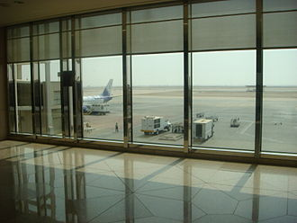 King Fahd International Airport - A Sama Airlines Boeing 737 parked at the airport, bound for Medina. View from the departure lounge of the terminal.