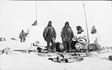 On the left is a snow cairn with flags. Three men are nearby, and assorted equipment is strewn on the snow.
