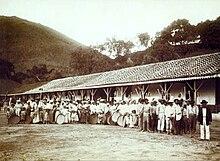 um grande grupo de homens, mulheres e crianças portadoras de implementos agrícolas e de pé na frente de um prédio longo e baixo com colinas crescentes em segundo plano