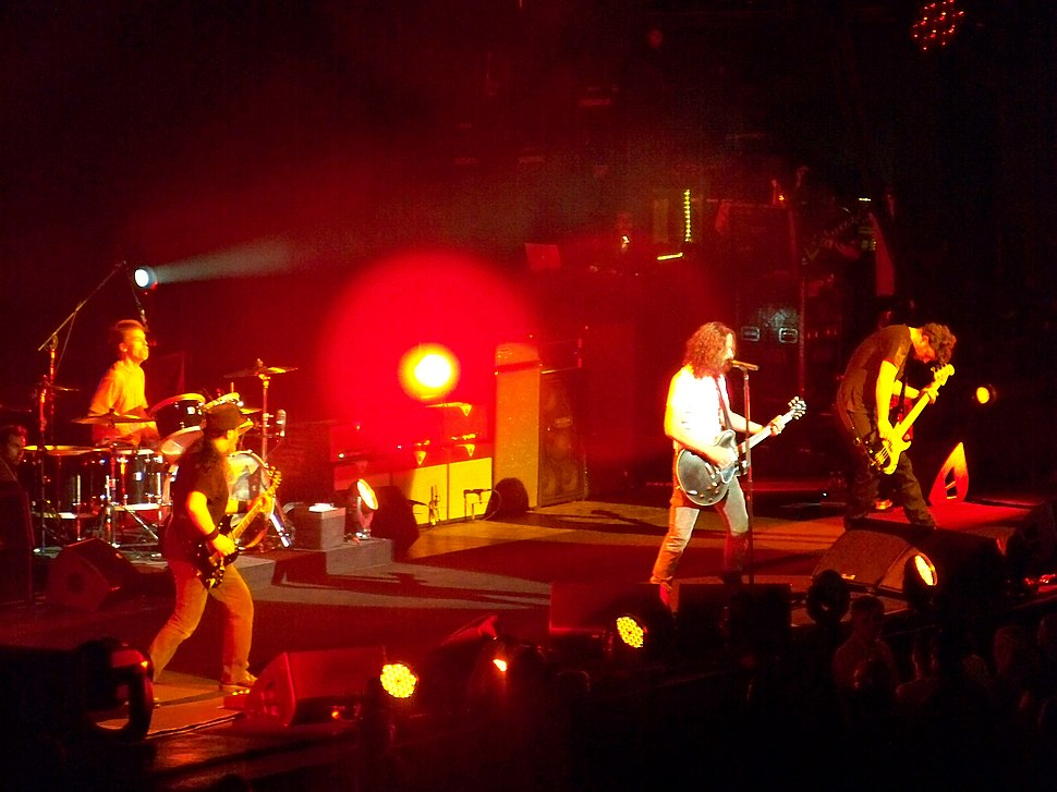 A rock band, Soundgarden, performing onstage. From left to right, a drummer playing drumkit, a guitarist (Kim Thayil), a singer also playing guitar, and an electric bassist. There are large, tall speaker cabinets onstage for the electric guitars and bass guitar.