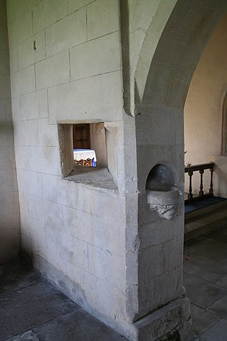 Hagioscope - Squint in wall of north aisle chapel, St Nicholas' Church, Walcot, Lincolnshire, looking towards south-east, with view of high altar in chancel beyond. Piscina supported by a man's head on jamb of wall
