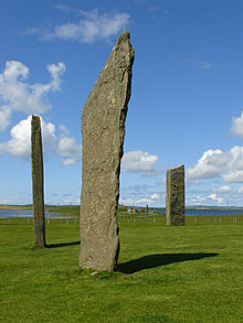 Three tall thin monoliths sit in a grassy field under blue skies with two bodies of water beyond at right and left.