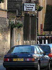 "A brown brick building in a city street with a sign that says ""Sylvia Young Theatre School"". In the foreground in a Ford Sierra car; in the background is some multi-coloured bunting."