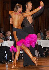 f4c1e4027c48 Latin dancers in their costumes. The woman is wearing backless dress with  deep slits on its lower portion, while the man is wearing a shirt with top  buttons ...