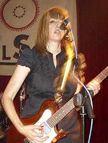 Shattuck playing bass guitar and singing into a microphone