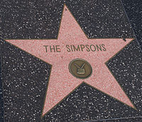 "A pink star engraved into a black tile. The words in the center of the star read ""THE SIMPSONS"", and below them is a pictogram of a television."