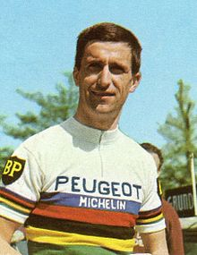 Tom Simpson wearing a white cycling jersey with horizontal rainbow stripes across the body