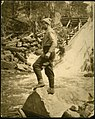Tom Thomson, standing on a rock fishing in moving water.jpg