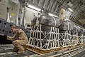 U.S. Air Force Tech. Sgt. Russell Johnson, a C-17 Globemaster III aircraft loadmaster with the 816th Expeditionary Airlift Squadron, guides a K-loader operator while loading container delivery systems inside his 130110-F-PM120-147.jpg