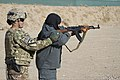 U.S. Army Sgt. 1st Class Edith Vaughn, left, with a female engagement team with Regional Command (South), acts as a safety for a female Afghan National Police recruit during an AK-47 rifle qualification course 131207-Z-TF878-001.jpg