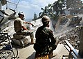 U.S. Navy Construction Mechanic Constructionman Brandon Winkleman, right, and U.S. Army Pfc. Aaron Sturm watch as rubble is excavated from the site of the Hotel Montana March 13, 2010, in Port-au-Prince, Haiti 100313-N-HX866-004.jpg