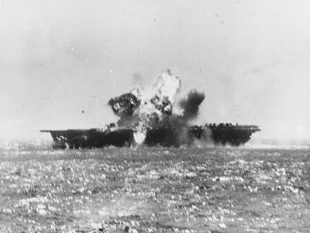 A kamikaze aircraft explodes after crashing into Essex's flight deck amidships 25 November 1944. USS Essex (CV-9) is hit by a Kamikaze off the Philippines on 25 November 1944.jpg