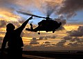 US Navy 041115-N-4757S-147 Aviation Electrician's Mate Airman John Broughton signals to an HH-60H Seahawk helicopter as it takes-off.jpg
