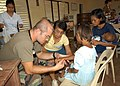 US Navy 050219-N-6775N-120 U.S. Army Capt. Michael Thwing, left, examines a young Filipino girl's wrist, after arriving at a school in Infanta, Philippines, during exercise Balikatan 2005.jpg