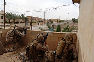 Suppressive fire - Two US Marines providing covering fire with a M4 carbine and a 40 mm M203 grenade launcher while a Marine from Air Naval Gunfire Liaison Company spots targets in Ramadi, Iraq, 2006.