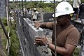 US Navy 070626-N-6410J-053 Senior Chief Builder James Brooks, from Naval Mobile Construction Battalion (NMCB) 7, carefully places a concrete block into place for a house being built in support of Pacific Partnership 2007.jpg