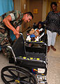 US Navy 070827-N-4238B-008 Equipment Operator 1st Class Manuel Gradillas presents Ana Renteria with a wheelchair he painted for her aboard Military Sealift Command hospital ship USNS Comfort (T-AH 20) while her caregiver, Maria.jpg