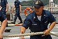 US Navy 080714-N-9123L-001 Interior Communications Electrician 3rd Class Mark Alejandro, from Lexington Park, Md., hauls in a mooring line.jpg
