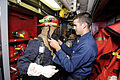 US Navy 100318-N-8335D-256 Mineman 2nd Class Corey Swartz, right, helps a Bangladesh navy sailor put on his firefighting gear during a drill aboard the mine countermeasures ship USS Patriot (MCM 7).jpg