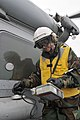 US Navy 110320-N-DM338-219 Machinist's Mate 1st Class Lucas Kasper, from Yorba Linda, Calif., scans an SH-60B Sea Hawk helicopter assigned to the W.jpg