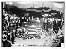 A casket flanked by uniformed men and others standing silently.