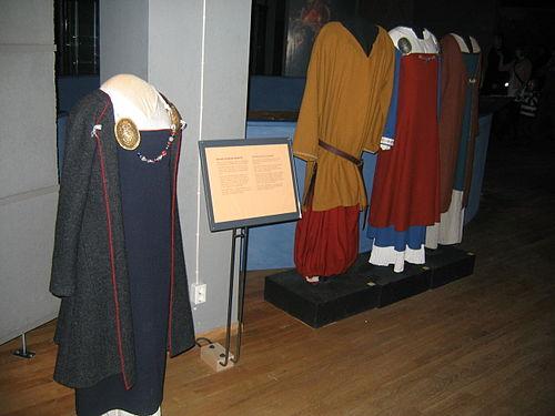 9a98ad33d816 Rekonstruktioner av vikingatida kläder på ett museum. Till vänster en  mörkblå hängselkjol under en något