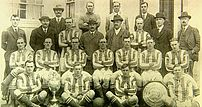 The West Bromwich Albion F.C. team of 1920 proudly display the 1919-20 League Championship trophy and the 1920 Charity Shield.