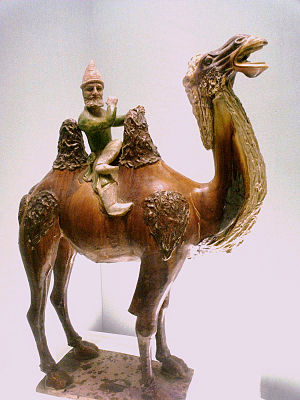 Sogdia - A Tang Dynasty Chinese ceramic statuette of a Sogdian merchant riding on a Bactrian camel