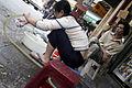 Woman washing dishes on sidewalk (3694377651).jpg