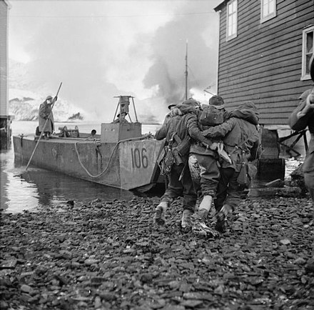A wounded soldier is helped onto an LCA Wounded being helped onto a landing craft.jpg