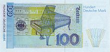 Banknote in light blue with yellowish green and beige, focused on an open grand piano, with a building in the left background
