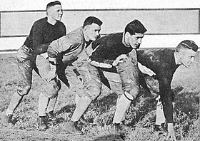 Four football players in uniform prepared to run, standing one behind the other