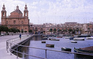 "Msida - ""On the harbour front of this fishing port, I became intrigued by the forest of TV aerials above the roof-tops next to the handsome Parish Church called the Church of Sultana tal-Paci, dedicated to St. Joseph. Msida is located along a creek, south of Gzira and west of Valletta."" Brian Harrington Spier, 1967"