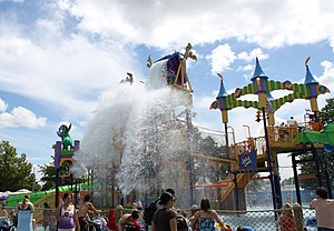Line of people standing behind a fence looking at a colorful amusement park ride which is splashed by water.