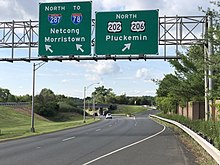 A multilane highway in a suburban area at a split, with two green signs over the road. The sign on the left reads north Interstate 287 to Interstate 78 Netcong Morristown with an arrow pointing to the upper right and the sign on the right reading north U.S. Route 202/U.S. Route 206 Pluckemin.