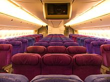 The interior of Biman's Boeing 777 aircraft showing the fronts of seats which are in various shades of indigo and violet.