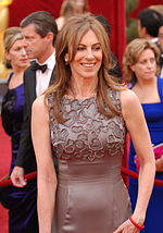A picture of a brunette. She wears a bluish grey dress and she smiles.