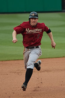 "A white man in a red baseball uniform running bases. Looking into the camera, he has on a red baseball uniform reading  ""Houston"" in yellow text with similarly-colored line under it. Below that to the runner's left hand side, there is a black ""2"" with a red outline. In addition to a black baseball with an orange star, he has on gray pants, black socks, and black cleats."