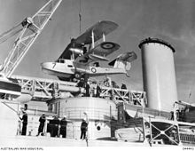 A biplane is being lowered onto a long, narrow, crossbeamed structure. The crane (the top of which is outside the photograph) is to the left, while an exhaust funnel is to the right.