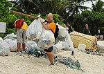 A Sailor collects trash on the beach.jpg