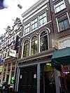 foto van Pand met gevel onder rechte lijst met gepleisterde lijsten in het gevelvlak en drie rondboogvensters op de eerste verdieping